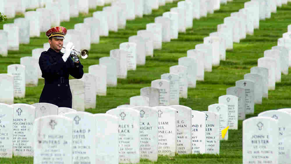 A bugler plays during a burial service at Arlington National Cemetery in Arlington, Va.