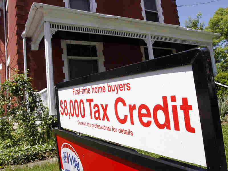 A sign promoting the $8,000 tax credit for first-time homebuyers is posted outside a home  for sale.