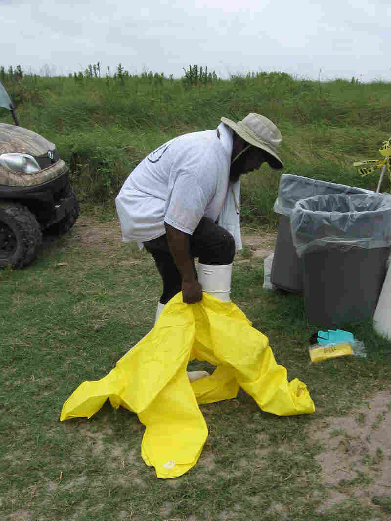 Jerome Benjamin of New Orleans slips into a yellow hazardous material suit.