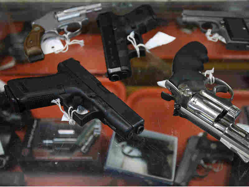Semi-automatic handguns and revolvers are seen on top of a glass display case at John Jovino Co.