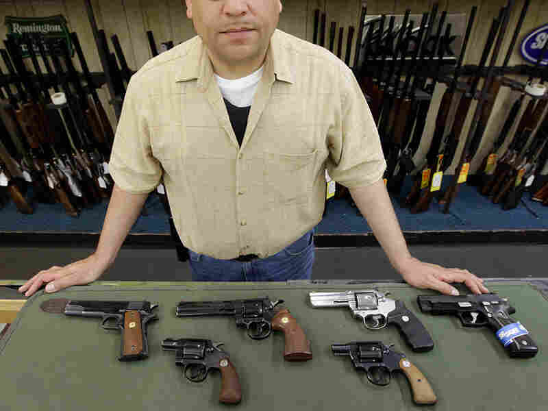 Mark Diaz, manager of Schrank's Smoke 'n Gun shop, displayed several handguns for sale at the store.
