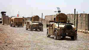 U.S. Army armoved vehicles leave their base after a handover ceremony outside Baghdad.
