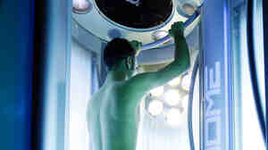 Joe Bongioni works on his tan in a tanning booth in New York.