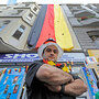 Ibrahim Bassal, Beirut-born shopkeeper, stands near the German flag displayed over his shop