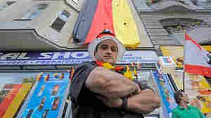 Ibrahim Bassal, Beirut-born shopkeeper, stands near the German flag displayed over his shop