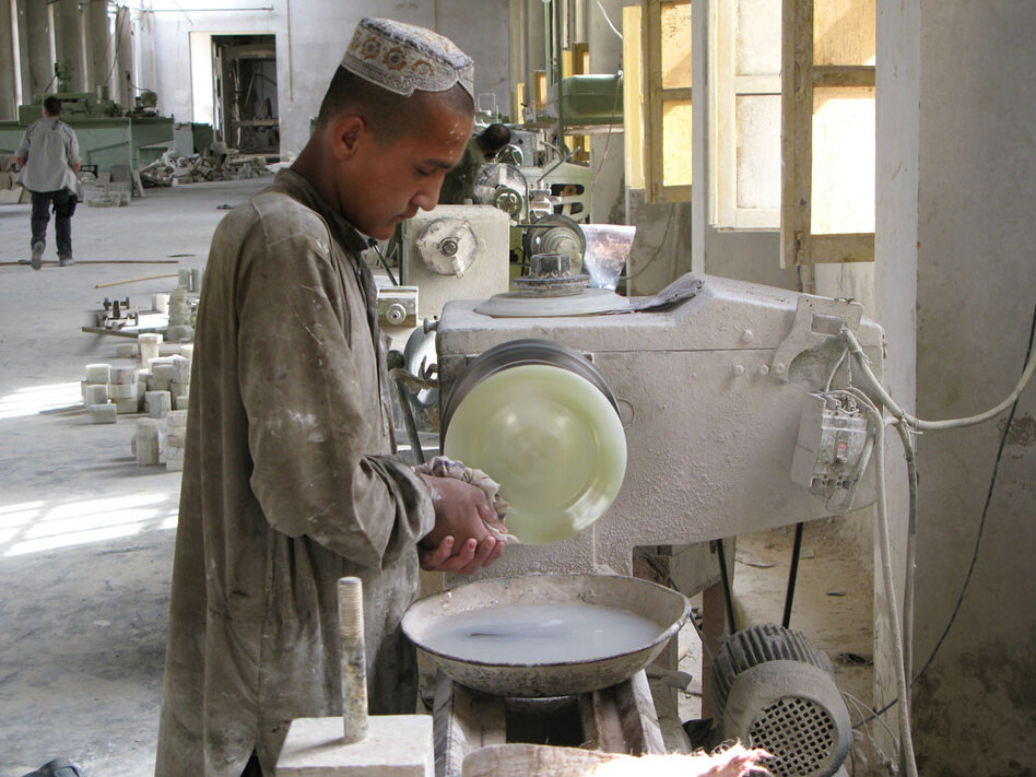 "A worker shapes an onyx plate at an Afghan stone-cutting factory. The plant -- in a part of Helmand province once known as ""Little America"" -- tripled its workforce after American workers upgraded a nearby hydroelectric dam."