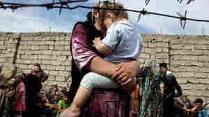 An ethnic Uzbek and her soon wait at the Kyrgyz-Uzbek border outside Suratash village