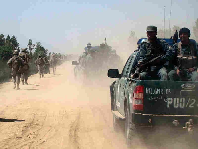 Afghan police and U.S. Marines patrol the city of Marjah