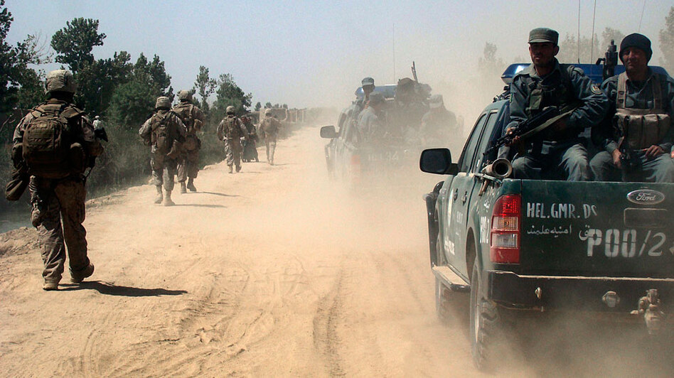 Afghan police and U.S. Marines patrol the city of Marjah in the Helmand province of Afghanistan in April 2010.