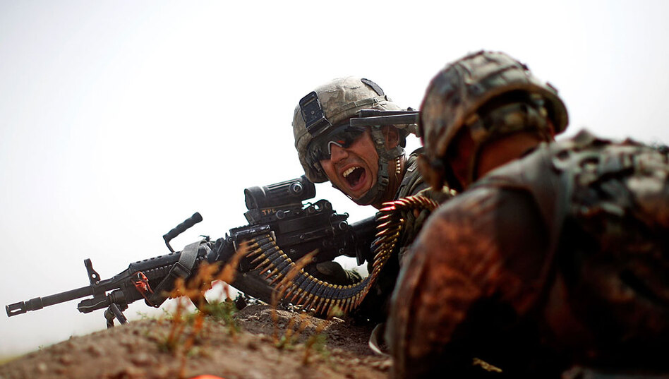 Spc. Jotiyar Saaty, with Bravo Company of the 101st Airborne Division, yells for more ammunition while trying to suppress heavy enemy fire near a village in the Pashmul area of Kandahar province. <!--EndFragment-->