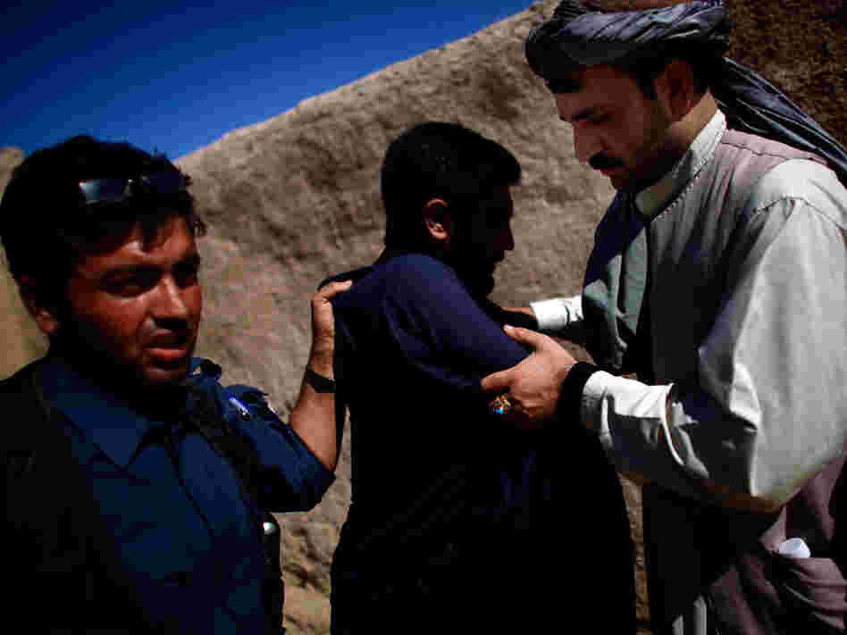 Afghan police officer (left) searches a man while local leader Karim Jan (right) holds his arms