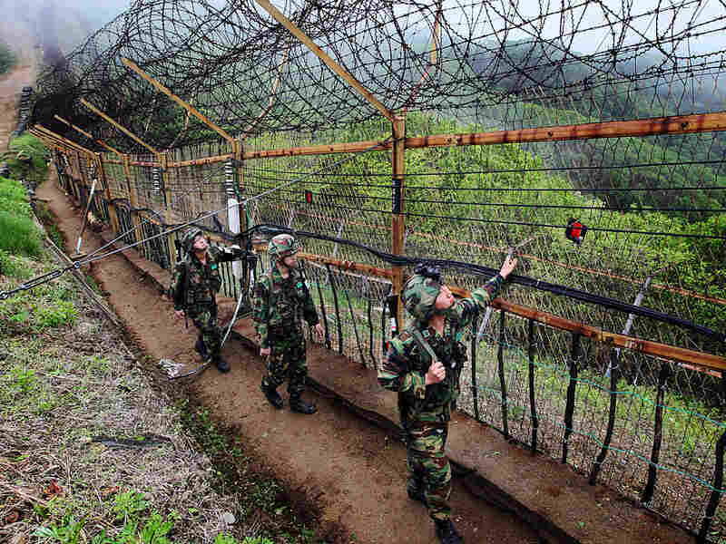South Korean soldiers patrol along a wire fence at border with North Korea