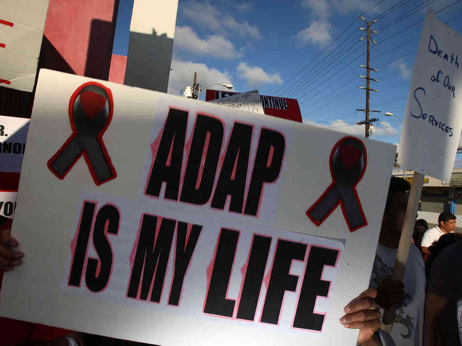 "A person holds a sign that reads ""ADAP is my life"" to protest cuts to AIDS services."