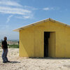 "A guard stands outside a prototype ""transitional"" housing model at a resettlement camp."