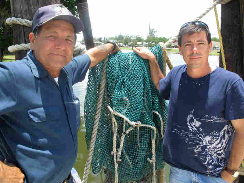 Anthony Chauvin, left, and his son, David, stand on where, until recently, they unloaded shrimp.