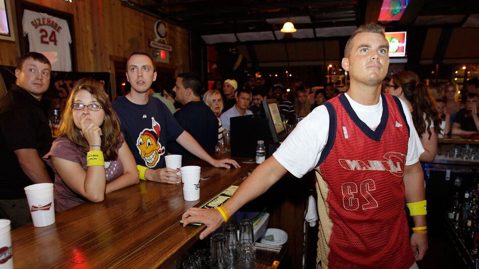 Cleveland bartender Dan Sampson (right) wears his LeBron James jersey inside-out after watching the NBA free agent announce that he would sign with Miami.