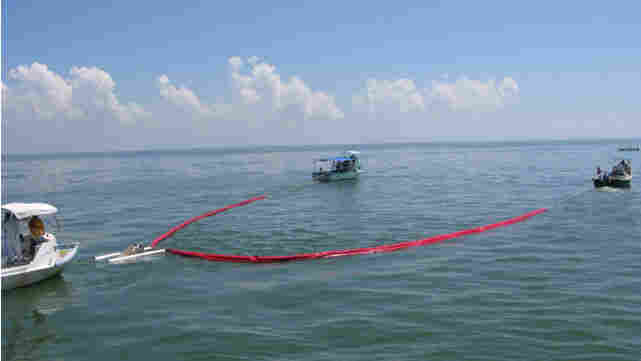 Two boats drag a containment boom, corralling a slick of oil in Mobile Bay, Ala.