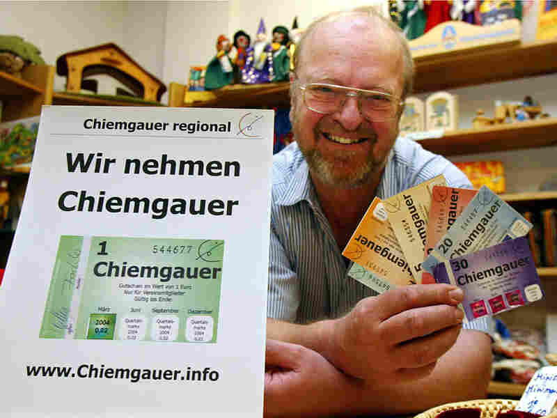 Shop owner displays the regional currency, chiemgauer, in Rosenheim in Germany's Bavaria