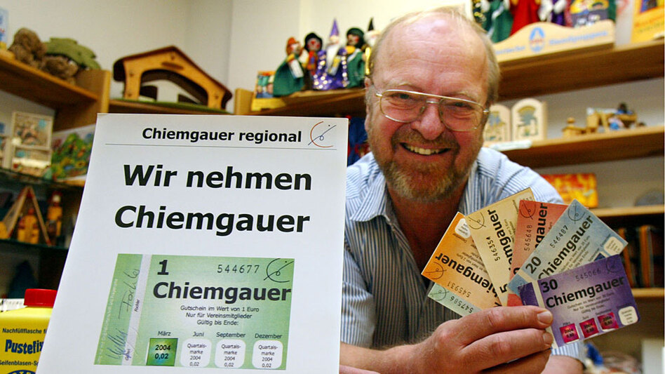 In this 2004 photo, Joseph Stoeckl, a shop owner in the town of Rosenheim, displays chiemgauer, a microcurrency in a region of Bavaria, Germany. The existence of the chiemgauer and some two dozen other regional currencies in Germany underscores the country's ambivalence toward the euro.