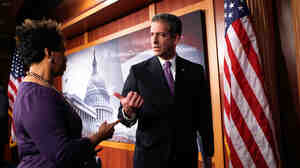 Sen. Russell Feingold (D-WI) talks to Rep. Barbara Lee (D-CA) after a news conference.