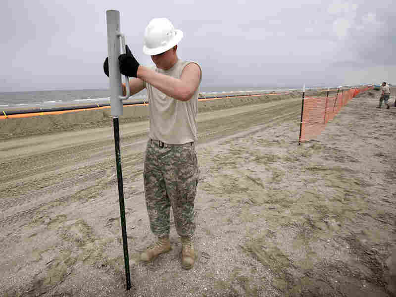 The Louisiana National Guard builds a fence near booms collecting oil  in Grand Isle, La.