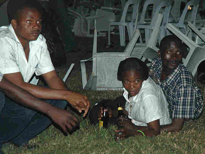 Survivors are seen at a restaurant in Kampala moments after a bomb blast
