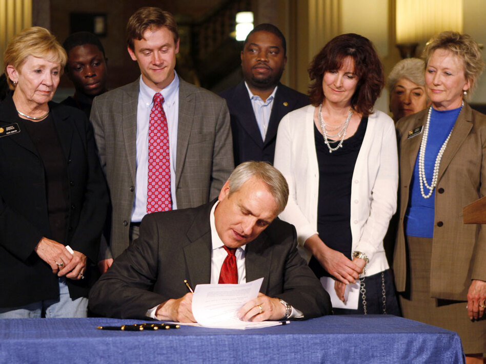 Colorado Gov. Bill Ritter, seated, signs a tenure bill that will judge teachers on student performance. Colorado has been a key state in nationwide efforts to evaluate and reward teachers based on student achievement.