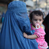 A burqa-clad woman carries a child through Kabul's old town