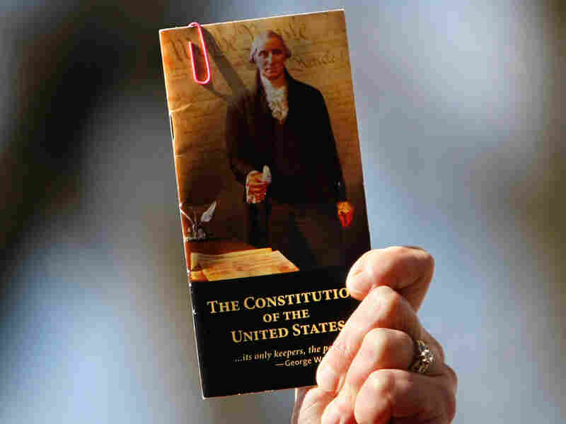 A rally participant holds up a pocket-sized copy of the U.S. Constitution.