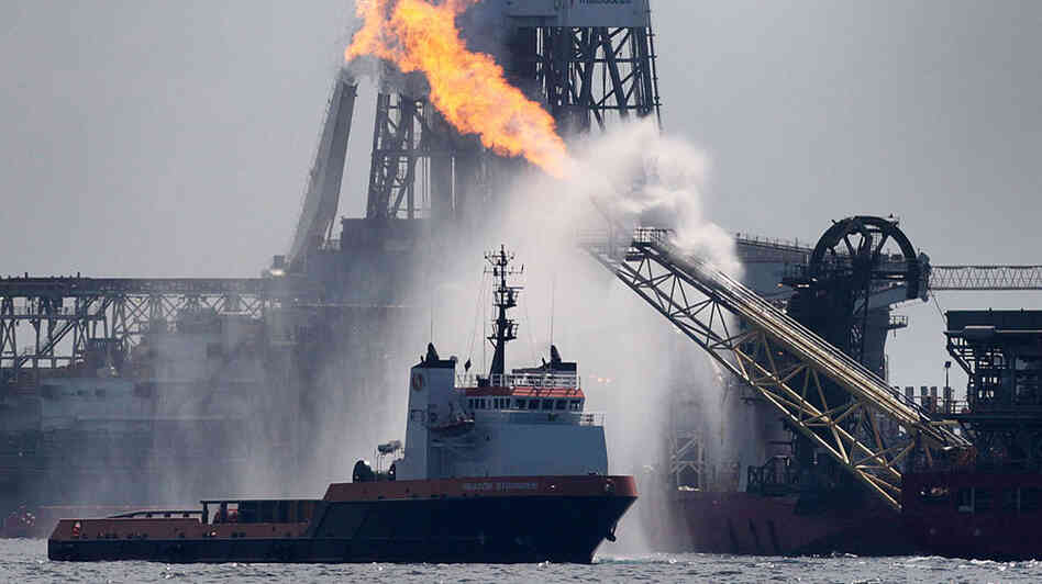 A work boat (left) operates near the Helix Producer as it burns off excess natural gas