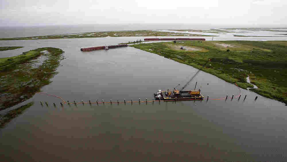 Barges lined up to block oil are seen from the air July 6 in The Rigolets