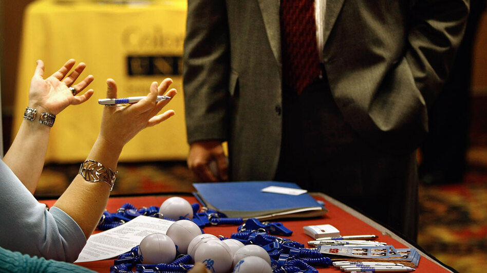 An employer speaks to a potential hire at a career fair in Denver.
