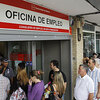People stand in line outside a government job center in Madrid