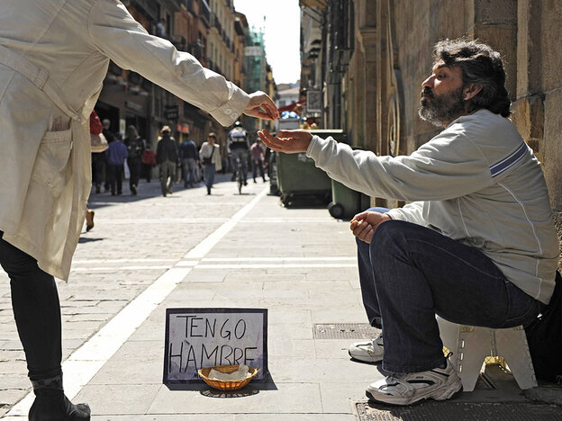"Jesus Torres, a 41-year-old unemployed construction worker and father of two, receives help from a passerby in Pamplona, Spain, in April. His sign reads: ""I'm hungry."""