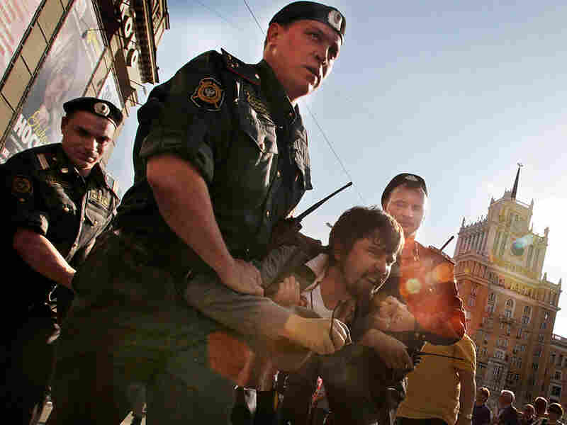Police carry a detained activist during a banned anti-Kremlin protest in Moscow in May