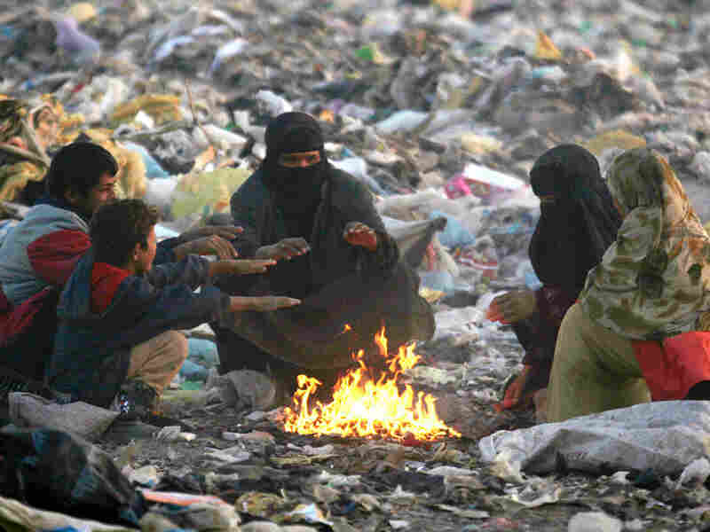 Iraqis sit next to a fire at a dump near Najaf, 100 miles south of Baghdad.