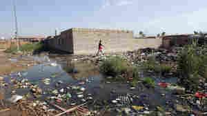 An Iraqi man walks past sewage and rubbish