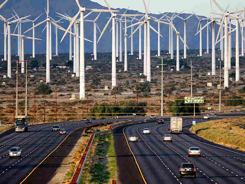 Wind turbines are seen in the background of traffic on Interstate 10, near Palm Springs, Calif.