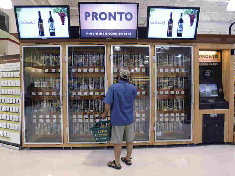 A shopper inspects wine kiosks in a Giant food store, the machines could expand to all of Pa.