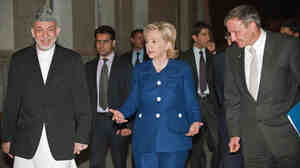 Secretary of State Hillary Clinton, right, is greeted by Afghanistan President Hamid K