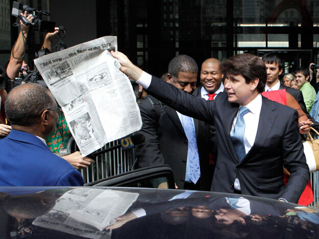 "Former Illinois Gov. Rod Blagojevich holds a dummy newspaper page that promises, ""And now ... the rest of the story."" However, Blagojevich's attorneys are debating whether to allow him to testify at his corruption trial."
