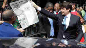 Former Illinois Gov. Rod Blagojevich holds a dummy newspaper page.