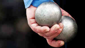 A player holds two Petanque balls.