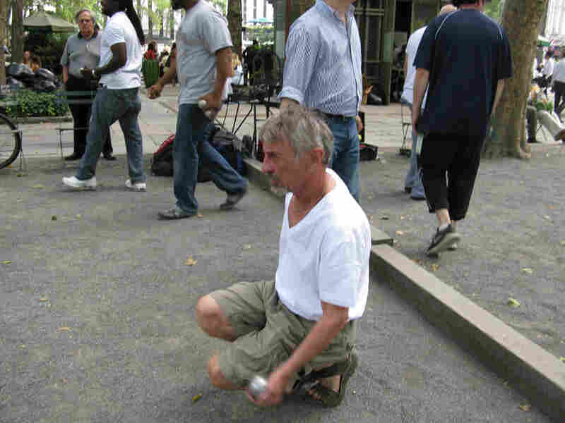 Yngve Biltsted prepares to toss a metal ball in a game of petanque in Bryant Park.