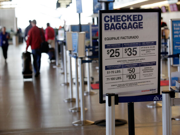A sign lists the costs for checking baggage with American Airlines last month at Seattle-Tacoma International Airport.