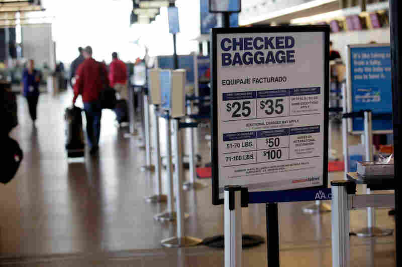 A sign lists the costs for checking baggage with American Airlines.