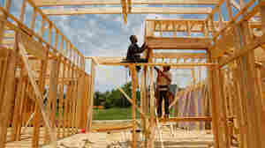 Construction workers frame a house