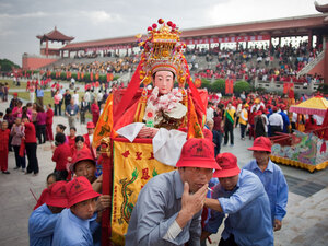 A village Mazu statue is carried into Meizhou Island's main square