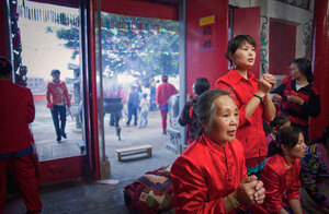 Women in lucky red outfits light incense and bow to a statue of Mazu the night before her birthday ceremony on Meizhou Island. Mazu worship is reinvigorating ancient traditions and bringing the local community together, as well as strengthening ties with Taiwan.