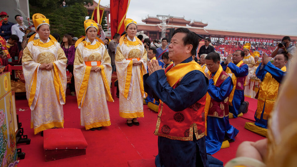 "Lin Jinbang, chairman of the island's main Mazu temple, bows during a ceremony for Mazu in the island's main square. ""Mazu is a heartfelt bridge linking Taiwan and the mainland,"" he says."